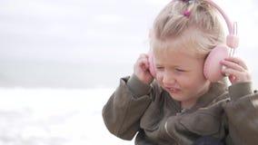 Menina bonito que escuta a música em fones de ouvido na praia video estoque