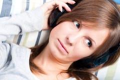 Menina bonito que escuta a música. Os olhos abrem Imagens de Stock Royalty Free