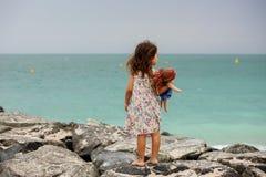 Menina bonito que está em pedras na praia em Dubai Imagem de Stock Royalty Free