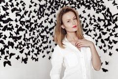 Menina bonito que está em um fundo fantástico com lotes das borboletas Imagem de Stock