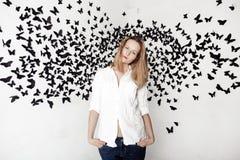 Menina bonito que está em um fundo fantástico com lotes das borboletas Foto de Stock Royalty Free