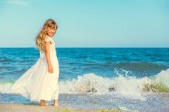 Menina bonito que está na praia do oceano Fotos de Stock Royalty Free
