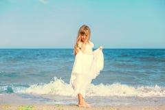 Menina bonito que está na praia do oceano Imagens de Stock Royalty Free