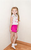 Menina bonito que está perto da parede Fotografia de Stock Royalty Free