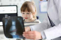 Menina bonito que fala com o gp que olha a imagem do raio X durante a consulta foto de stock