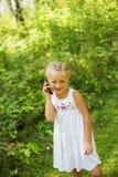 Menina bonito que fala no telefone no parque em um dia ensolarado do verão Fotos de Stock Royalty Free