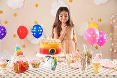 Menina bonito que faz o desejo antes de fundir para fora velas em seu bolo de aniversário dentro Imagens de Stock