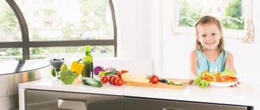 Menina bonito que faz a salada Cozimento da criança Alimento saudável Imagem de Stock