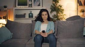 Menina bonito que gerencie na tevê com o assento de observação de controle remoto no sofá em casa vídeos de arquivo
