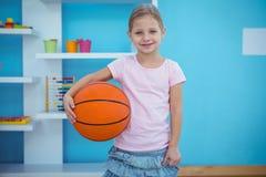 Menina bonito que guarda a bola da cesta Imagem de Stock