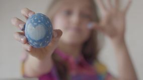 Menina bonito que guarda o ovo da p?scoa azul com cora??o pintado ? disposi??o, mostrando o ? c?mera O foco move-se do filme