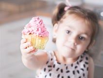 Menina bonito que guarda queques do aniversário na cozinha Conceito festivo e do feriado Imagens de Stock Royalty Free