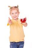 Menina bonito que guardara de vidro com sorriso do suco Fotografia de Stock Royalty Free