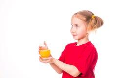 Menina bonito que guardara de vidro com sorriso do suco Imagem de Stock Royalty Free