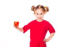Menina bonito que guardara de vidro com sorriso do suco Foto de Stock