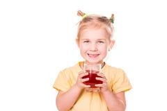 Menina bonito que guardara de vidro com sorriso do suco Fotos de Stock Royalty Free