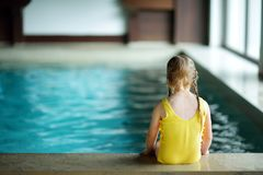 Menina bonito que joga com anel inflável na piscina interior Aprendizagem nadar Criança que tem o divertimento com brinquedos da  fotos de stock