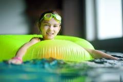 Menina bonito que joga com anel inflável na piscina interior Aprendizagem nadar Criança que tem o divertimento com brinquedos da  fotografia de stock royalty free
