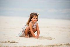 Menina bonito que joga com a areia na praia em Dubai Imagem de Stock