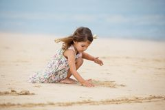 Menina bonito que joga com a areia na praia em Dubai Fotos de Stock