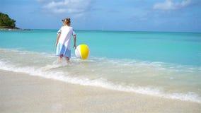 A menina bonito que joga com a bola na praia, verão das crianças ostenta fora video estoque