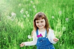 Menina bonito que joga com bolhas de sabão no gramado verde exterior, conceito feliz da infância, criança que tem o divertimento Fotografia de Stock Royalty Free