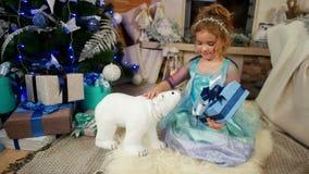 A menina bonito que joga com brinquedos e presentes, presente do Natal, embalou belamente na caixa de papel com uma curva, presen filme