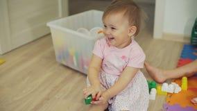 Menina bonito que joga com brinquedos e sorriso filme