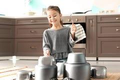 Menina bonito que joga com kitchenware fotografia de stock