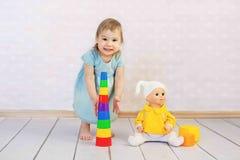 Menina bonito que joga com os brinquedos que sentam-se no assoalho no fundo de madeira Fotografia de Stock Royalty Free