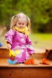 Menina bonito que joga em uma caixa de areia Fotografia de Stock Royalty Free
