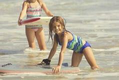 Menina bonito que joga no oceano em uma placa da dança Fotos de Stock Royalty Free