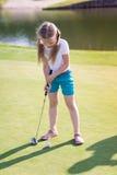 Menina bonito que joga o golfe em um campo Fotografia de Stock Royalty Free
