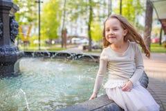 Menina bonito que joga pela fonte da cidade no dia de verão quente e ensolarado Criança que tem o divertimento com água no verão  imagem de stock