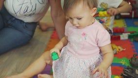 Menina bonito que joga tijolos com sua mãe filme