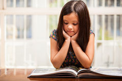 Menina bonito que lê um livro de histórias Imagem de Stock