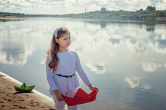 Menina bonito que levanta com os barcos de papel no lago fotografia de stock royalty free