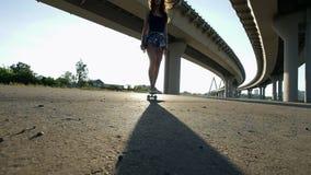 A menina bonito que monta um skate sob a ponte na noite, o sol brilha vídeos de arquivo