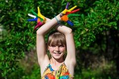 Menina bonito que mostra suas mãos pintadas em cores brilhantes Mãos pintadas brancas de passeio Imagens de Stock Royalty Free