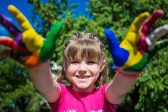Menina bonito que mostra suas mãos pintadas em cores brilhantes Mãos pintadas brancas de passeio Foto de Stock Royalty Free