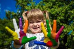 Menina bonito que mostra suas mãos pintadas em cores brilhantes Mãos pintadas brancas de passeio Imagens de Stock