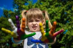 Menina bonito que mostra suas mãos pintadas em cores brilhantes Mãos pintadas brancas de passeio Fotografia de Stock