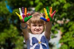 Menina bonito que mostra suas mãos pintadas em cores brilhantes Mãos pintadas brancas de passeio Imagem de Stock Royalty Free
