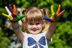 Menina bonito que mostra suas mãos pintadas em cores brilhantes Mãos pintadas brancas de passeio Imagem de Stock