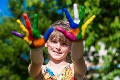Menina bonito que mostra suas mãos pintadas em cores brilhantes Mãos pintadas brancas de passeio Fotos de Stock