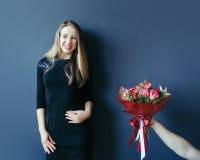 Menina bonito que obtém o ramalhete de tulipas vermelhas Noivo que dá tulipas Imagens de Stock Royalty Free