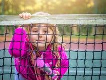 Menina bonito que olha através da rede do tênis fotografia de stock