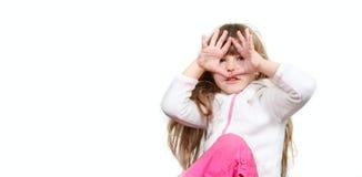 Menina bonito que olha através de seus dedos Imagem de Stock