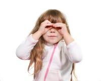 Menina bonito que olha através de seus dedos Foto de Stock Royalty Free