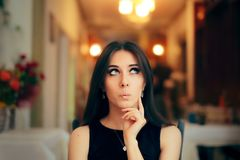 Menina bonito que pensa sobre seu plano no partido de jantar foto de stock